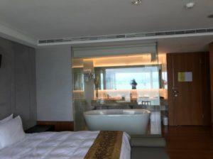 台湾SPAホテルのベッドルームと、ガラス張りの浴室の写真