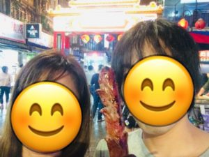 台湾饒河街観光夜市の「牌門」前で豚肉のソーセージを持っている二人